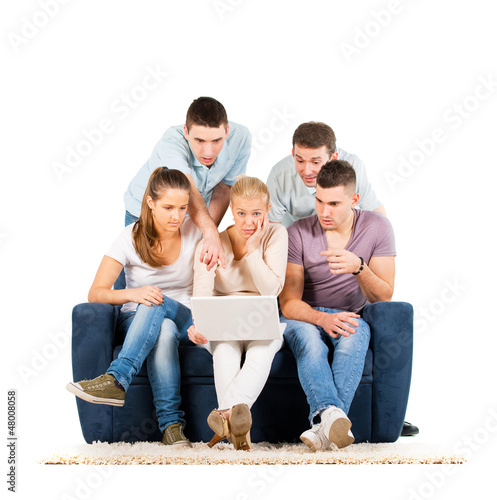 Young people sitting on a sofa, looking at a laptop