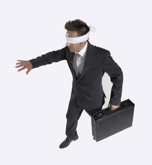 Hombre de negocios vendado,ciego caminando sujetando un maletín.
