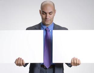 Ejecutivo sujetando dos paneles blancos.