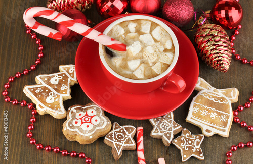 Cup of coffee with Christmas sweetness on wooden table close-up