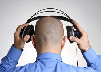 Hombre utilizando audífonos,colocando audífonos.