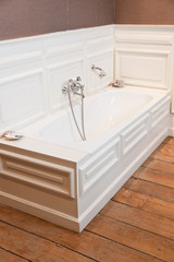 Classic bath with old tap in white bathroom.