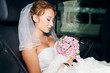 bride posing with bouquet in luxurious car in her wedding day