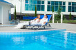 couple posing on deck chair in luxurious hotel and swimming pool