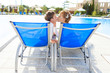 bride and groom posing on deck chair background swimming pool