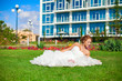 Young bride with bouquet posing in park lying on green grass
