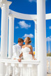 wedding: couple on beach in area with white columns, blue sky