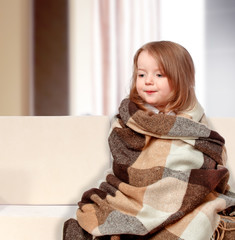 girl dressed in a blanket sitting on the couch