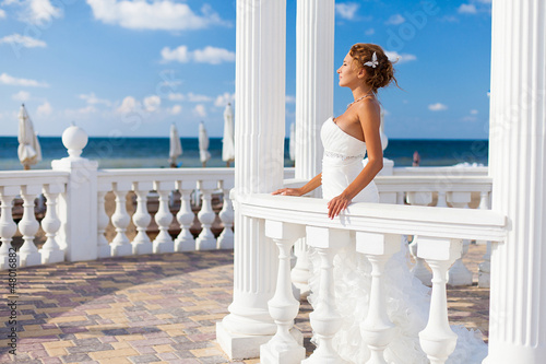 bride posing on beach in white columns on background of blue sky