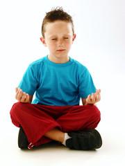 Niño meditando,sereno haciendo yoga.