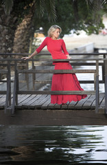 Beutiful woman in red dress, wooden bridge