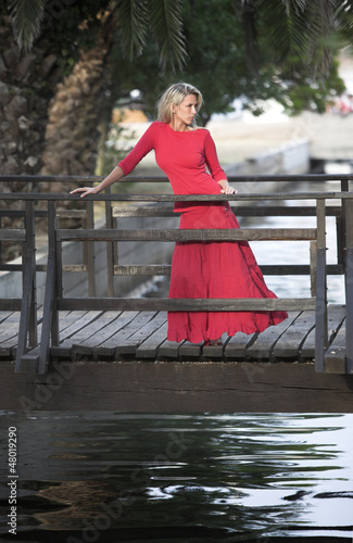 Beutiful woman in red dress, wooden bridge