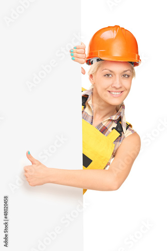 Female worker giving a thumb up and standing behind panel