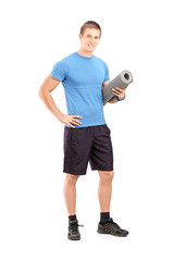 Full length portrait of a male athlete holding a mat