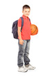 School boy with backpack holding a  basketball