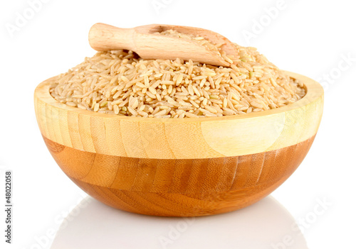brown rice in a  brown wooden plat, isolated on white