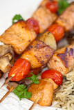 Salmon kebab with tomato, mushrooms and rice. Macro.
