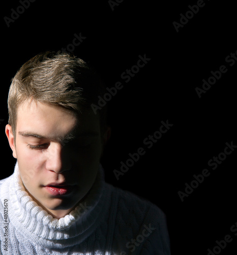 Close-up of young man on black background, low key,