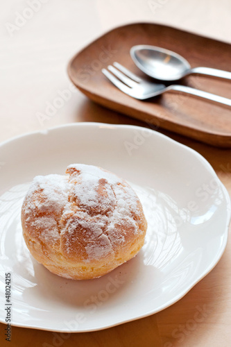 Choux pastry cream puffs on white plate