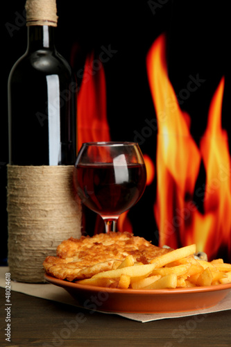 Roast chicken cutlet with french fries, glass of wine