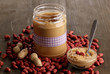 Delicious peanut butter in jar on wooden table close-up