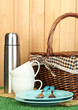 metal thermos with cups, plates and basket