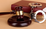 Gavel, handcuffs and.book on law on beige background