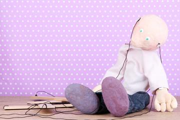 Wooden puppet sitting on polka dot background