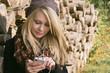 Mädchen beim Musik hören vor Brennholzstapel