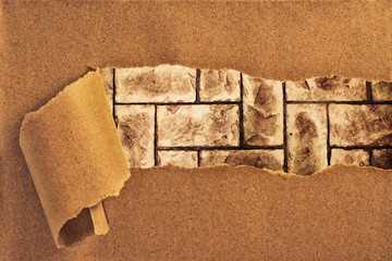 brick wall behind torn recycled paper