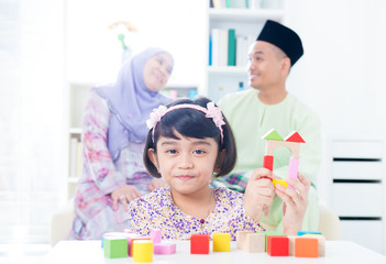Muslim child building toy wooden house.