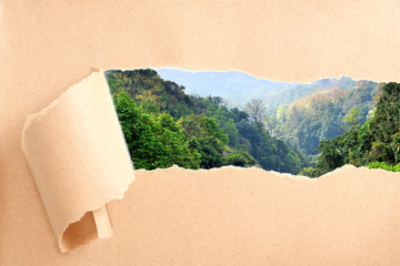 Mountain view behind torn recycled paper