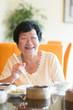 Senior Asian Woman dining