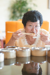 Senior Asian Woman dining at restaurant