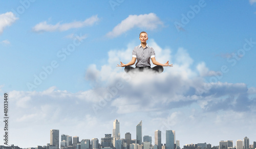 Businesswoman meditating sitting on the cloud