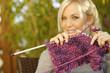 Hübsche Frau mit Strickzeug auf der Terrasse