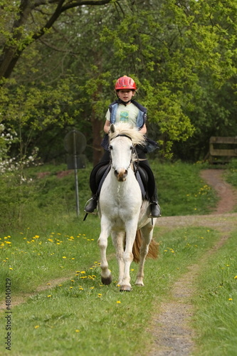 Mädchen im Galopp auf ihrem Pony