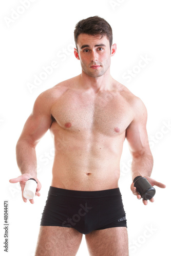 sexy male body builder holding a boxes with supplements on his b