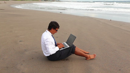guy in office suit printing on laptop sitting on the beach