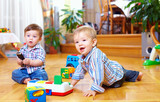 Fototapety two cute baby boys playing with toys at home