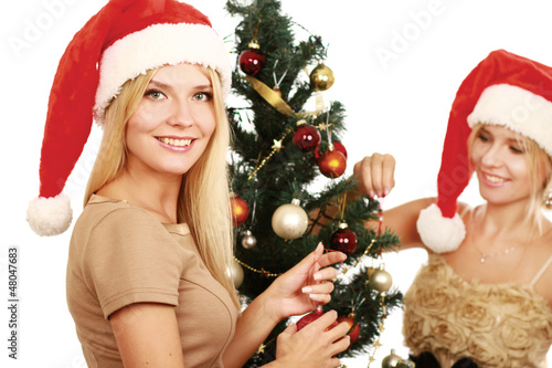 Two girlfriends in santa hat and near Christmas tree