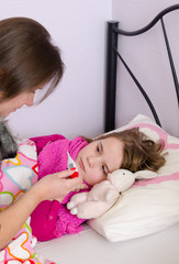 Mother check temperature of sick daughter
