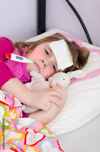 Sick young girl under temperature measurement