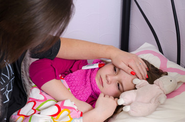 Mother taking care about sick sleeping daughter