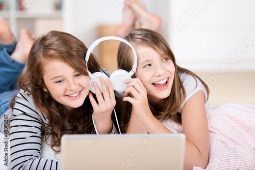 zwei mädchen hören zusammen musik