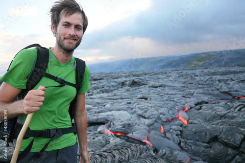 Hawaii hiker hiking by flowing lava