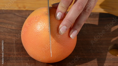 woman hand cut fresh ripe grapefruit pomelo fruit two piece
