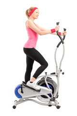 Female athlete working on a cross trainer machine