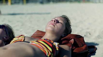Sexy women lying on the beach and sunbathing