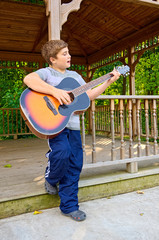 Boy Playing Guitar Outdoors
